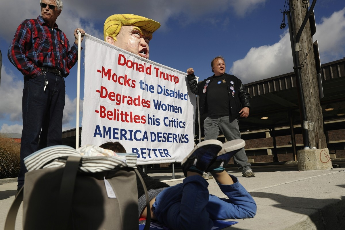 Supporters pose with a large effigy of Donald Trump while waiting to attend a campaign event with Hillary Clinton in Detroit, Michigan.