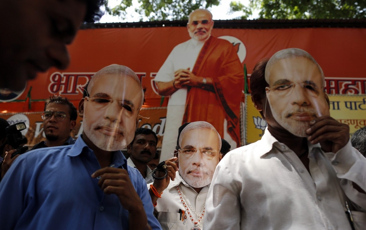 Supporters of Hindu nationalist Narendra Modi, prime ministerial candidate for India's main opposition Bharatiya Janata Party (BJP), wear masks depicting Modi outside their party office in Mumbai