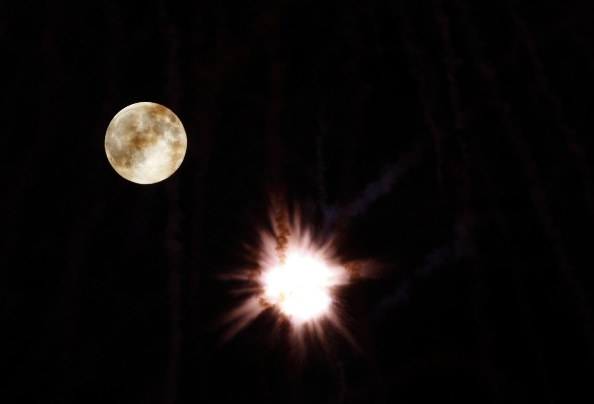 A fireworks petard explodes in front of the supermoon outside the town of Mosta, celebrating the feast of its patron saint, in central Malta, August 10, 2014.
