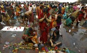 Hindu women worship after taking a holy dip in the Ganges river on the occasion of Guru Purnima in Kolkata, India.