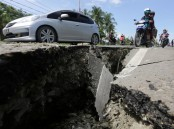 Motorcyclists pass a damaged section of a road following an earthquake in Meuredu, Pidie Jaya, in the northern province of Aceh, Indonesia.