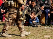 Displaced Iraqis wait for checks by Iraqi forces in western Mosul.