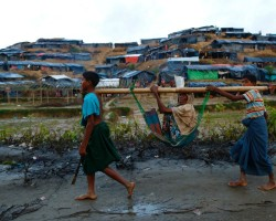 Rohingya refugee children carry an old woman in a sling near Balukhali makeshift refugee camp in Cox's Bazar, Bangladesh.