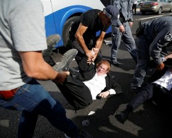 Israeli policemen carry away ultra-Orthodox Jewish men as they try to block a road during a protest against the detention of members of their community who failed to report to a military recruiting office, near Modiin, Israel.