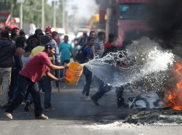 A man throws water on burning tires during a protest against the rising prices of gasoline enforced by the Mexican government at the side of a Pemex gas station in San Miguel Totolcingo, Mexico.
