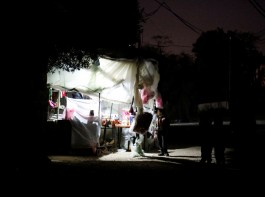 A Palestinian boy stands outside a makeshift grocery shop lit with a lamp powered by a battery during a power cut in Beit Lahiya in the northern Gaza Strip.