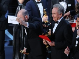 Jordan Horowitz of La La Land holds the card announcing Moonlight as the winner of the Best Picture Oscar as presenter Warren Beatty and show host Jimmy Kimmel stand behind.