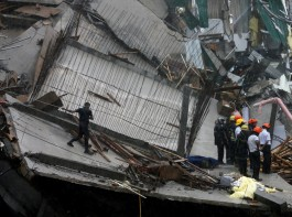 Military officials and fire brigade members work during a rescue mission in Colombo.