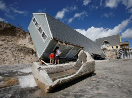 Local residents look inside a collapsed coastal house in Vilano Beach.