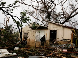 A man looks for valuables in the damaged house of a relative after the area was hit by Hurricane Maria in Guayama, Puerto Rico.