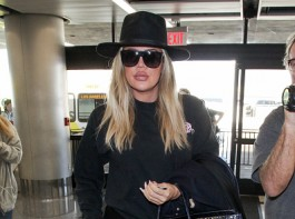 Reality star Khloe Kardashian hides her growing baby bump at the Los Angeles International Airport.