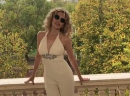 Flawless Kylie Minogue flaunts her figure in a perilously plunging jumpsuit.