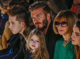 Former England captain David Beckham sits next to U.S. Vogue editor Anna Wintour (2nd R) with his daughter, Harper, on his lap and son Brooklyn (L)