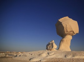 A woman walks near a rock formation known as 'Mushroom Rock' in the White Desert north of the Farafra Oasis southwest of Cairo. The White Desert, about 500 km southwest of the Egyptian capital Cairo, features limestone and chalk forms strangely shaped by the wind and sand, a terrain that gains in intensity when illuminated by the moon. Slightly to the north lies the Black Desert, given its name by the volcanic rock dolerite, similar to basalt. Four-by-four and trekking trips for tourists include Bedouin music around campfires and nights slept under a breathtaking array of stars.