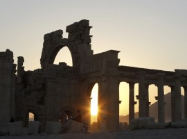 The sun sets behind ruined columns at the historical city of Palmyra in the Syrian desert northeast of the capital of Damascus.
