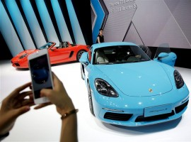 The latest models and concept cars are unveiled at Auto China 2016 in Beijing. A visitor takes pictures of a new Porsche 718 Cayman S presented during Auto China 2016 auto show.