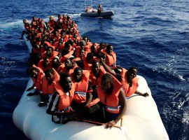 An overcrowded dinghy with migrants is followed by members of the German NGO Jugend Rettet as they approach the Iuventa vessel during a rescue operation.