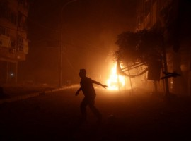 A man runs near a burning car after an airstrike in the rebel held Douma neighborhood of Damascus.