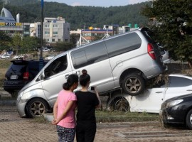 Women take a photograph of cars damaged by typhoon Chaba in Ulsan, South Korea.