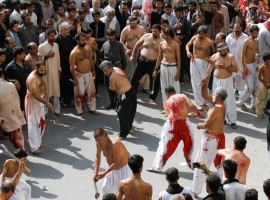 Men participate in self flagellation during the Shi'ite Muharram procession in Peshawar, Pakistan.
