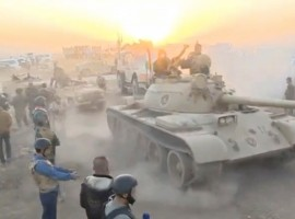 Tanks move past soldiers in military fatigues as the sun begins to set east of Mosul, where the Iraqi government launched a U.S.-backed offensive to drive Islamic State from the northern city, in this still image taken from video released October 17, 2016.