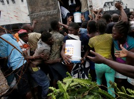People fight for a bucket of supplies during a distribution after Hurricane Matthew in Torbeck, Haiti.