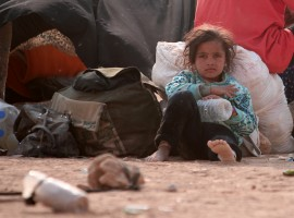 A refugee girl rests, among Iraqi refugees that fled violence in Mosul and internally displaced Syrians whom fled Islamic State controlled areas in Deir al-Zor, near the Iraqi border, in Hasaka Governorate.