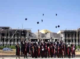 New graduates of Engineering and Law faculties at Benghazi University celebrate as they pose in front of damaged buildings at their university's former headquarters, which was destroyed during clashes in 2014, between members of the Libyan National Army and Shura Council of Libyan Revolutionaries, an alliance of former anti-Gaddafi rebels who have joined forces with Islamist group Ansar al-Sharia, in Benghazi, Libya.
