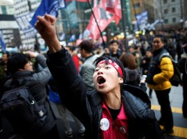 A member of Korean Confederation of Trade Unions shouts in front of Samsung's main building as they march during a general strike calling for South Korean President Park Geun-hye to step down, in central Seoul, South Korea November 30, 2016.