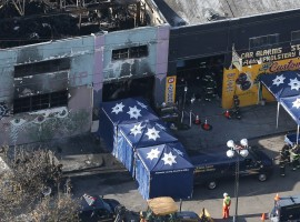 A coroner's truck is seen outside the burned warehouse following the fatal fire in the Fruitvale district of Oakland, California.