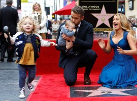 Actor Ryan Reynolds kisses his daughter while posing by his star with his wife Blake Lively and their daughter James on the Hollywood Walk of Fame in Hollywood, California U.S., December 15, 2016.