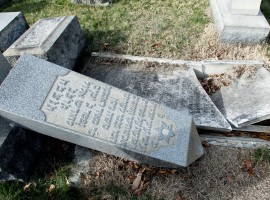 A headstone, pushed off its base by vandals, lays on the ground near a smashed tomb in the Mount Carmel Cemetery, a Jewish cemetery, in Philadelphia, Pennsylvania. About 100 headstones were knocked over, police said, in an incident that apparently took place after dark on February 25.