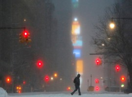 Times Square is seen in the background as a man walks along West 59th street in falling snow in Manhattan.