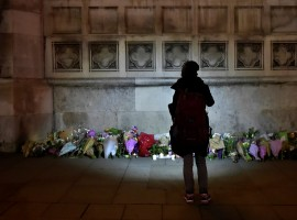 A woman looks at floral tributes laid in Westminster the day after an attack in London.