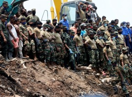 Members of the military wait until another rescue team recovers a dead victim during a rescue mission after a garbage dump collapsed and buried dozens of houses in Colombo, Sri Lanka April 16, 2017.