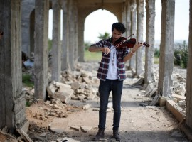 Ameen Mukdad, a violinist from Mosul who lived under ISIS's rule for two and a half years where they destroyed his musical instruments, performs at Nabi Yunus shrine in eastern Mosul, Iraq, April 19, 2017.