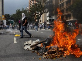 An opposition demonstrator walks while clashing with riot police during the so called