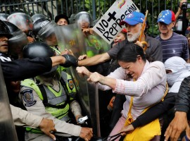 Opposition supporters confront riot security forces while rallying against President Nicolas Maduro in Caracas, Venezuela. Venezuela's elderly have been hard hit by four years of brutal recession, leading to shortages of food and medicines, long lines at shops and runaway prices.