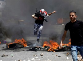 A Palestinian protester jumps over burning tyres during clashes with Israeli troops at a protest marking the 69th anniversary of Nakba, near the Jewish settlement of Beit El, near the West Bank city of Ramallah.