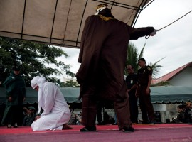 An Indonesian woman is publicly caned for spending time with a man who is not her husband, in Banda Aceh, Aceh province, Indonesia.