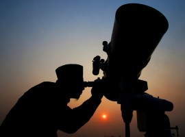 An official looks through a telescope for the sighting of the new moon for the start of Ramadan at a religious boarding school in Jakarta, Indonesia May 26, 2017.
