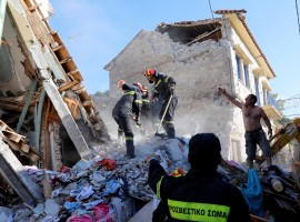 Rescue team members search for victims at a collapsed building in the village of Vrissa on the Greek island of Lesbos, Greece, after a strong earthquake shook the eastern Aegean.