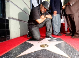 Rapper Ice Cube poses by his star after it was unveiled.