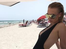 Swimwear Designer Bianca Elouise puts on busty display in plunging black bikini.