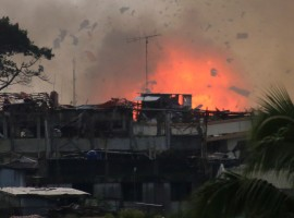Debris and fire is seen after an OV-10 Bronco aircraft released a bomb, during an airstrike, as government forces continue their assault against insurgents from the Maute group, who have taken over large parts of Marawi City.