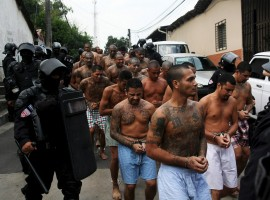 Members of the Mara Salvatrucha gang are guarded by policemen upon their arrival at the Quezaltepeque jail in Quezaltepeque.