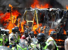 Riot security forces members congregate next to a government truck that was set on fire during a rally against Venezuelan President Nicolas Maduro's government in Caracas, Venezuela June 22, 2017.