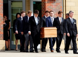 The casket of Otto Warmbier is carried to the hearse followed by his family and friends after his funeral service at Wyoming High School in Wyoming, Ohio.