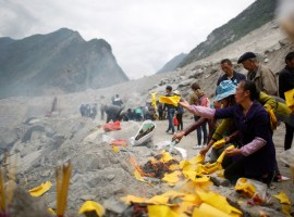 Relatives of victims burn incense and paper money to mourn their dead relatives at the site of a landslide in the village of Xinmo, Mao County, Sichuan Province.