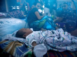 An evacuated newborn sleeps inside a mosquito net at an evacuation center outside Marawi, as government forces continue their assault against insurgents from the Maute group in Marawi, Philippines.